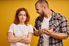 Furious bearded guy screams and gestures angrily, yells at woman, have dispute, pose together over yellow background. Strict boss royalty free stock photos