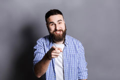 Furious bearded man shouting loud, point at camera. Furious bearded man shouting loud and point at camera. Young angry guy screaming at you, gray studio Royalty Free Stock Images