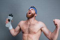 Furious bearded sportsman with bottle of water standing and shouting. Furious bearded young sportsman with bottle of water standing and shouting over grey Stock Photos