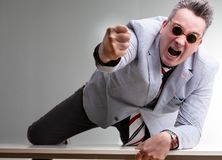 Furious belligerent man punching the camera. Furious belligerent man punching towards the camera leaning across the table in a show of aggression and domination royalty free stock images