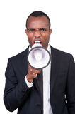 Furious boss. Angry young African man in formalwear shouting at megaphone while standing isolated on white background Royalty Free Stock Photography