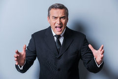 Furious boss. Furious mature man in formalwear gesturing and looking at camera while standing against grey background Royalty Free Stock Images
