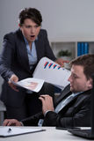 Furious boss. Young furious female boss and her scared young employee Stock Photography