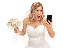 Furious bride looking at her cell phone Stock Photography
