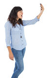 Furious brunette holding her mobile phone and screaming. On white background Royalty Free Stock Photos
