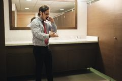Furious Business Man Screaming On Cell Phone In Office Restroom stock images