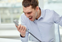 Furious businessman calling on phone in office Stock Photos