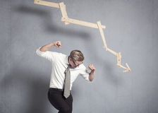 Furious businessman in front of graph pointing down. Stock Images