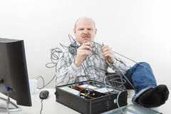 Furious Businessman Holding Tangled Cables Of Computer At Desk Stock Photography