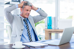 Furious businessman looking at laptop computer Stock Images