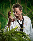 Furious businessman on the phone lost in jungle Stock Image