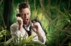 Furious businessman on the phone lost in jungle Royalty Free Stock Images