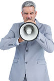 Furious businessman posing with loudspeaker and looking at camera Stock Photo