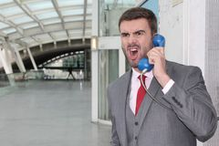 Furious businessman screaming on public phone.  Royalty Free Stock Images