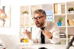 Furious businessman showing to laptop. Annoyed furious bearded businessman in glasses and earphones sitting at office table and showing to laptop while knowing royalty free stock photo