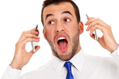 Furious businessman talking on two phones royalty free stock photography