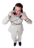 Furious businessman tangle up in phone wires Stock Photos