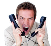 Furious businessman tangle up in phone wires Stock Image