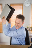 Furious businessman about to smash his laptop Stock Photo
