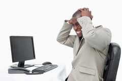 Furious businessman using a monitor. Against a white background Royalty Free Stock Photo