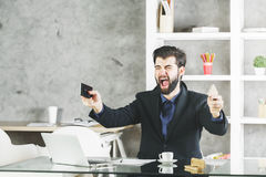 Furious businessman using two cellphones. Young businessman with furious face expression using two cellphones at workplace with laptop, coffee cup and supplies Royalty Free Stock Image