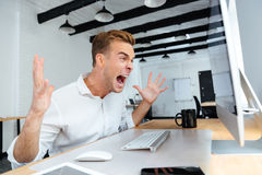 Furious businessman working with computer and shouting. Furious angry young businessman working with computer and shouting Stock Image