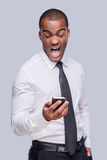 Furious businessman. Furious young African man in shirt and tie holding mobile phone and shouting while standing against grey background Stock Photo