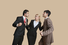 Furious businessmen in conflict with woman trying to resolve over colored background. Furious businessmen in conflict with women trying to resolve over colored Royalty Free Stock Images