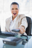Furious businesswoman screaming while hanging up the phone. In bright office Royalty Free Stock Images