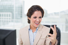 Furious businesswoman shouting at smartphone Stock Images