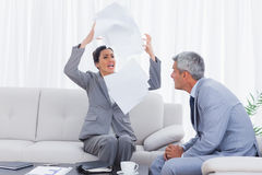 Furious businesswoman throwing documents with colleague watching. On the sofa in office Royalty Free Stock Photography