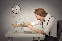 Furious businesswoman throws a punch into computer, screaming. Angry, furious businesswoman throws a punch into computer, screaming. Negative human emotions Stock Image