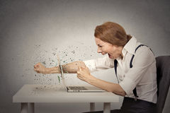 Furious businesswoman throws a punch into computer, screaming. Angry, furious businesswoman throws a punch into computer, screaming. Negative human emotions royalty free stock photo