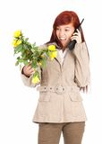 Furious calling young woman with flowers Royalty Free Stock Images