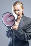 Furious Caucasian Blond Female in Suite Shouting Using Megaphone Stock Image