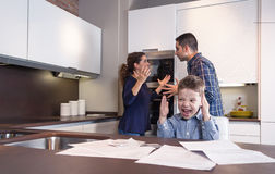 Furious child screaming and parents in a quarrel. Furious child screaming and his parents having hard discussion in a home kitchen by couple difficulties. Family Stock Image