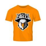 Furious eagle head athletic club vector logo concept isolated on orange t-shirt mockup.  Stock Image