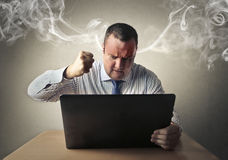 Furious employee. Trying to destroy his laptop Stock Photos