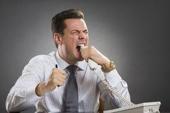 Furious executive biting phone receiver. Furious frustrated executive wearing white shirt and tie biting phone receiver while showing an enraged face grimace Royalty Free Stock Photo