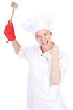 Furious female cook keeping wooden hammer Royalty Free Stock Images