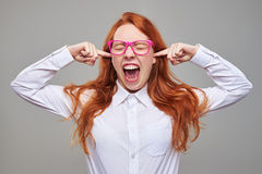 Furious girl closing ears with index fingers. Close-up of furious girl closing ears with index fingers. Posing in the studio. Isolated over background. Red hair Stock Images