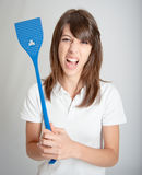 Furious girl with flyswatter Royalty Free Stock Photo