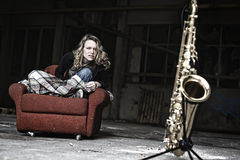 Furious girl starring at saxophone. Groovy girl sitting in shabby sofa starring aggressively at saxophone in old run-down factory Stock Photo
