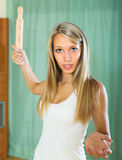 Furious girl swinging arm with rolling-pin Royalty Free Stock Images