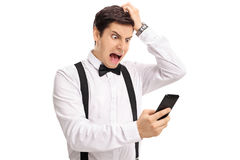 Furious groom looking at a phone Stock Photography