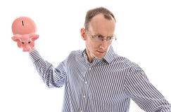 Furious isolated bald man smashing his piggy bank. Royalty Free Stock Images
