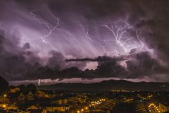 The furious lightning falling next to a quiet town. royalty free stock image