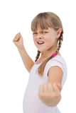 Furious little girl. Showing her fist on white background Royalty Free Stock Image