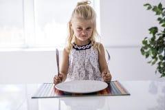 Furious little girl waiting for dinner. Holding a fork in the hand. A Furious little girl waiting for dinner. Holding a fork in the hand royalty free stock image
