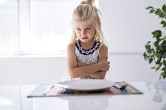 A very Furious little girl waiting for dinner. A Furious little girl waiting for dinner stock photo